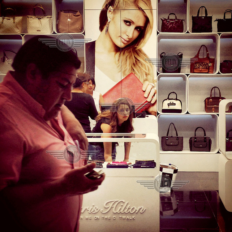 People shop for bags at a Paris Hilton store in the Scala Mall.