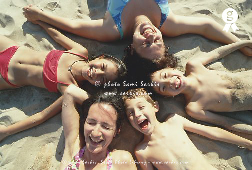 Two women and three children (6-9) lying on beach, heads in circle (Licence this image exclusively with Getty: http://www.gettyimages.com/detail/200387987-001 )