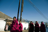 Monks wait in the streets before Tibetan Buddhist Monks of the Gelugpa Order (Yellow Hat Sect) carry a thangka (painting of Buddha) through the streets of Xiahe, Gansu Province, China, during the Monlam Festival at the Labrang Monastery.  Monks work on the painting for the year preceding the festival and then display it on a nearby hillside for about an hour.