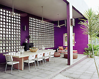 The covered terrace takes up one side of a courtyard garden and is used as an outdoor dining room with a long stone table seating eight