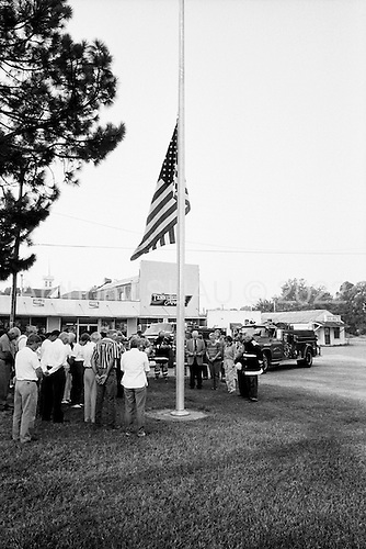 September 11, 2002<br /> Grand Junction, Tennessee<br /> <br /> Marking the moment that terrorist first impacted a passenger airplane into the World Trade Centers, one year earlier, firemen in the small town of Grand Junction, population 300, raise the town flag in honor of the victims.