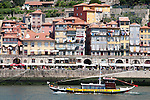 A colorful boat offering tourists a ride on the Douro River in Porto, Portugal as it passes the Ribeira section of the city.