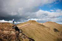 Female hiker hiking in mountains of Brecon Beacons national park with view of Pen Y Fan and Corn Du, Wales