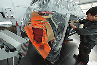 "Switzerland. Canton Geneva. Plan-les-Ouates. Renault Retail Group, RRG Suisse. ""Spot-repair"" by Dells Angels. Renault Clio car inside a paint booth in auto body repair garage. After filling bumpy part and grinding automobile car body in garage workshop, the mechanic worker uses a color spectrophotometer for automotive paint. He needs to know exactly the mixed of colors to match the car's paint. The spot repaired area is warmed in prepping for paint. 4.03.2020 © 2020 Didier Ruef"