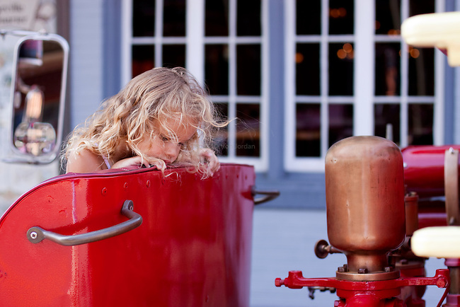 Imagination. A cute little girl looking at old red firetruck steam engine.