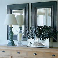 In the living room a rectangular silver plant container has been arranged in front of a pair of dark-framed mirrors contrasting with the blond wood of the cupboard