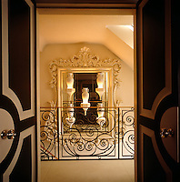 View through the open double doors to the staircase landing and a collection of illuminated vases displayed against an ornate carved mirror