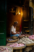 A vegetable vendor waits for customers at a market stall in the New Market area of Kolkata, India, on Friday, May 26, 2017. Photographer: Sanjit Das