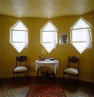 In the master bedroom an antique table and chairs sit under three of the unusual hexagonal-shaped windows