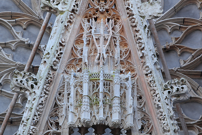 Detail of the sculpture on the gable of the Western facade with the Western rose window behind, at Rouen Cathedral or the Cathedrale de Notre Dame de Rouen, built 12th century in Gothic style, with work continuing through the 13th and 14th centuries, Rouen, Normandy, France. Picture by Manuel Cohen