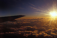 Sunset over clouds seen from airplane with wing in frame