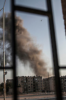 A Syrian army helicopter flies in circles the sky as a plume rises from the FSA headquarters that is shelling by Syrian army aircraft at the residential neighborhood of Tarik Albab.
