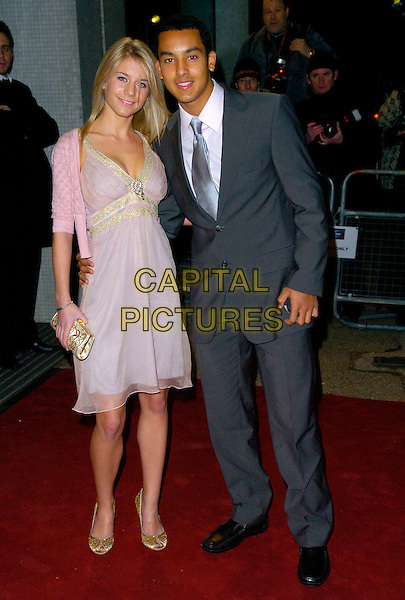 "MELANIE SLADE & THEO WALCOTT.Arrives at ""An Audience With Take That"".at The London Television Studios,.London, England, December 2nd 2006..full length pink cardigan dress gold clutch bag couple.CAP/CAN.©Can Nguyen/Capital Pictures"