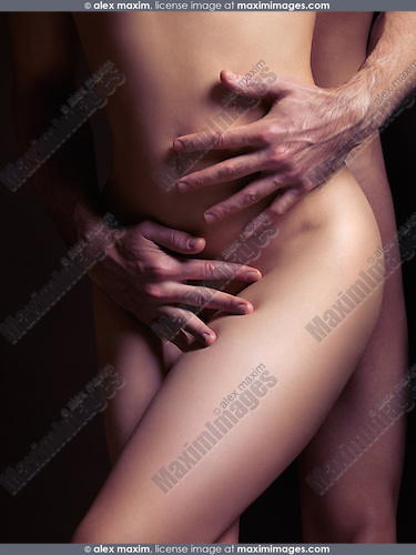 Sensual couple artistic photo. Man hands embracing naked woman body.