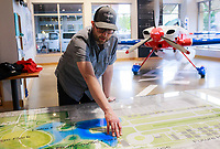 NWA Democrat-Gazette/CHARLIE KAIJO Phillip Johnson, director of OZ1, points at a map of the grounds of the new Flying Club that will be built by the end of the summer, Friday, July 6, 2018 at the OZ1 Flying Club pop-up shop in Bentonville. <br />