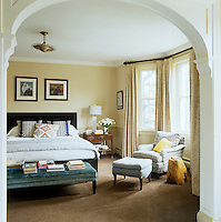 The master bedroom is furnished with a velvet upholstered bench and a comfortable armchair
