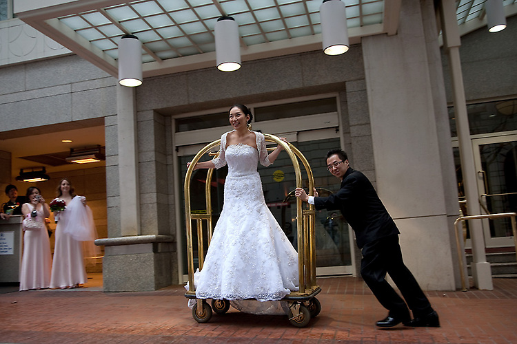 Groom pushes bride in front of Hilton Hotel