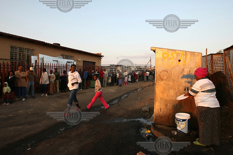 A woman uses a water tap as people stand in a long line outside a polling station in Diepsloot, Johannesburg waiting to cast their votes in the 2009 general election.
