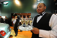 A server carries champagne following the Bentley presentation at the Detroit Auto Show in Detroit, Michigan on January 11, 2009.