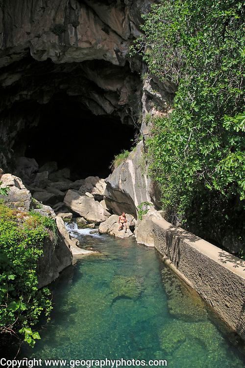 Person exploring entrance ot cave, Cueva del Gato, Benaojan, Serrania de Ronda, Malaga province, Spain