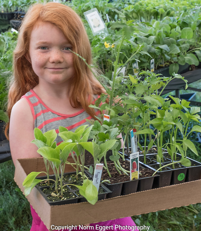 Cute little red headed girl shopping for garden plants in the spring with her mother