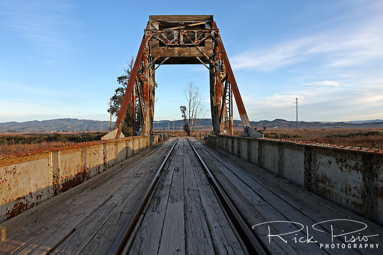The Wingo Drawbridge crosses Sonoma Creek near the ghost town of Wingo. Located in Northern California, in the marshes north of San Pablo Bay, Wingo was once a railroad connection point for visitors arriving by steam boat from San Francisco. The Wingo Drawbridge is one of the few examples of a Scherzer Rolling Bridge, a design that has no pivots or hinges. When opened to water traffic the span rolls like a rocking chair, only further. The bridge was built in the 1920's by the Toledo Bridge & Crane Co. and is typical of that period before welding came into general use.