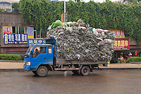Daytime landscape view of a supply truck loaded with empty burlap bags driving on Hui Long Jie in Lóngmǎtán Qū of the Lúzhōu Prefecture City in Sichuan Province.  © LAN