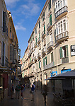 People walking through narrow streets with tall historic buildings in the city centre of Malaga, Spain