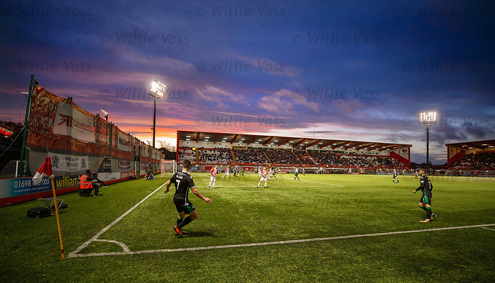 John McGinn floats in a corner kick for Hibs as the winter sun sets at Hamilton