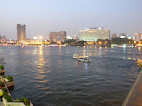 Nile River scene at dusk, Cairo Egypt with skyline in the background.