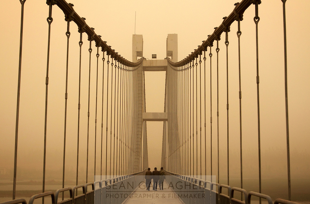 Local men walking across a bridge that has been engulfed by a sandstorm near the city of Zhongwei, in Ningxia Province. Increasing desertification in the region has resulted in more sandstorms which continue to plague this region, especially in the spring months.
