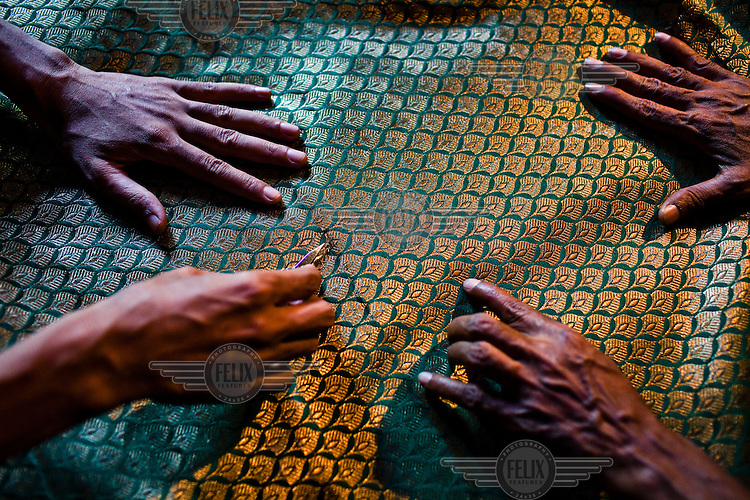 Weavers cut small threads out of the final silk piece in their workspace in Gazi Sadullahpura Bade Bazaar in Varanasi.