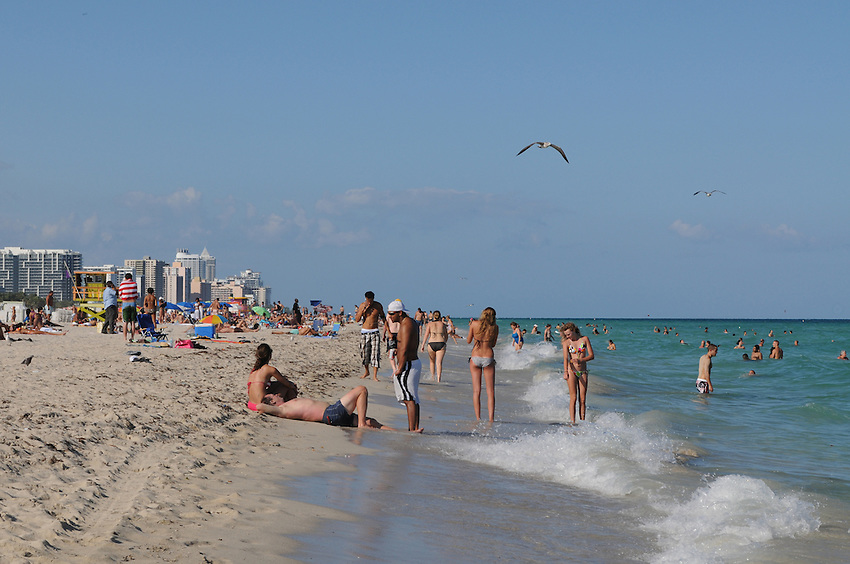 People enyoying the sun sand and warm ocean waters of beautiful South Beach Miami Beach Florida.