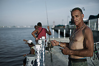 Images from the old Havana, Cuba, Latin America.  ..Alcides is just another of the many Cubans who love to fish.  He fishes every day, from sunset to dusk.  ..The many kilometers of malecon are crowded with fishermen.  In fact, this is such an important activity in the island, that one told me with a serious and stoic face, 'I love this more than women'.
