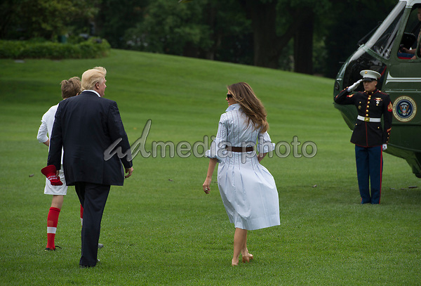 United States President Donald J. Trump walks to Marine One with first lady Melania and their son Barron, as they depart the White House for Camp David, the Presidential retreat near Thurmont, Maryland, in Washington, DC, USA, 17 June 2017. Photo Credit: Michael Reynolds/CNP/AdMedia