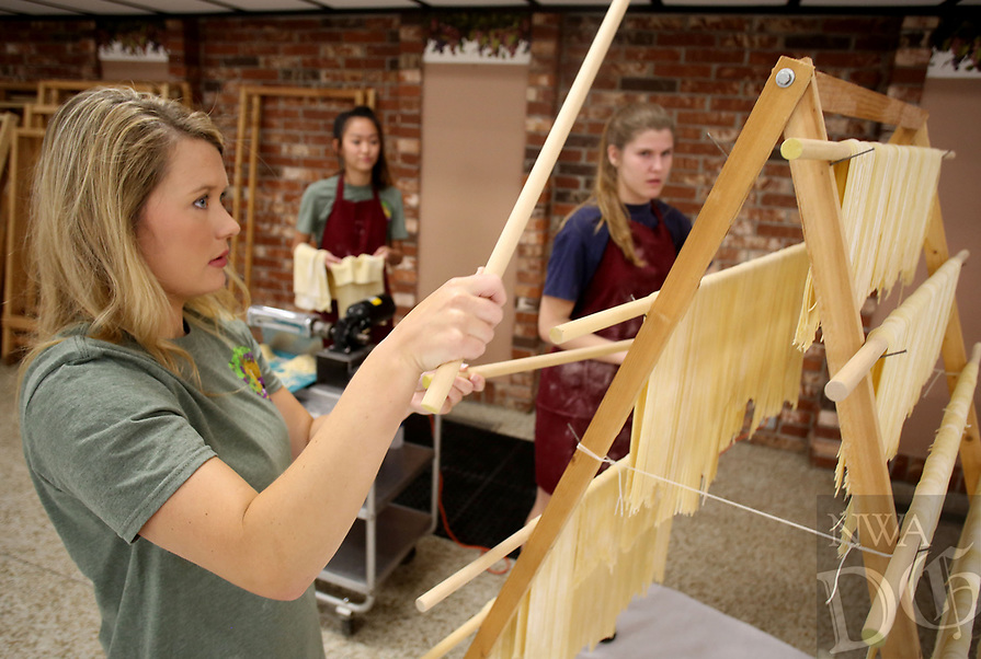NWA Democrat-Gazette/DAVID GOTTSCHALK   Ashley Wiedenhoeft (cq) (from left) rearranges the dowels Monday, July 10, 2017, on a rack to continue to hang fresh pasta noodles with Hannah Pianalto, 14, and Mary Kidd, 15, at the St. Joseph's Parish Hall in Tontitown. More than 3,000 pounds of pasta noodles are being prepared for the 119th Tontitown Grape Festival which runs Tuesday, August 1 thru Saturday August 5. The homemade spaghetti will be served August 3 thru Aug. 5. For more information see tontitowngrapefestival.com.
