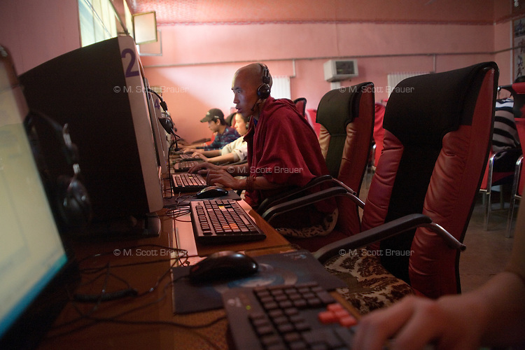 A young Tibetan Buddhist monk uses a computer at an internet cafe in Xiahe, Gansu, China.  Xiahe, home of the Labrang Monastery, is an important site for Tibetan Buddhists.  The population of the town is divided between ethnic Tibetans, Muslims, and Han Chinese.