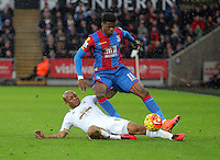 Wilfried Zaha of Crystal Palace is tackled by Andre Ayew of Swansea during the Barclays Premier League match between Swansea City and Crystal Palace at the Liberty Stadium, Swansea on February 06 2016