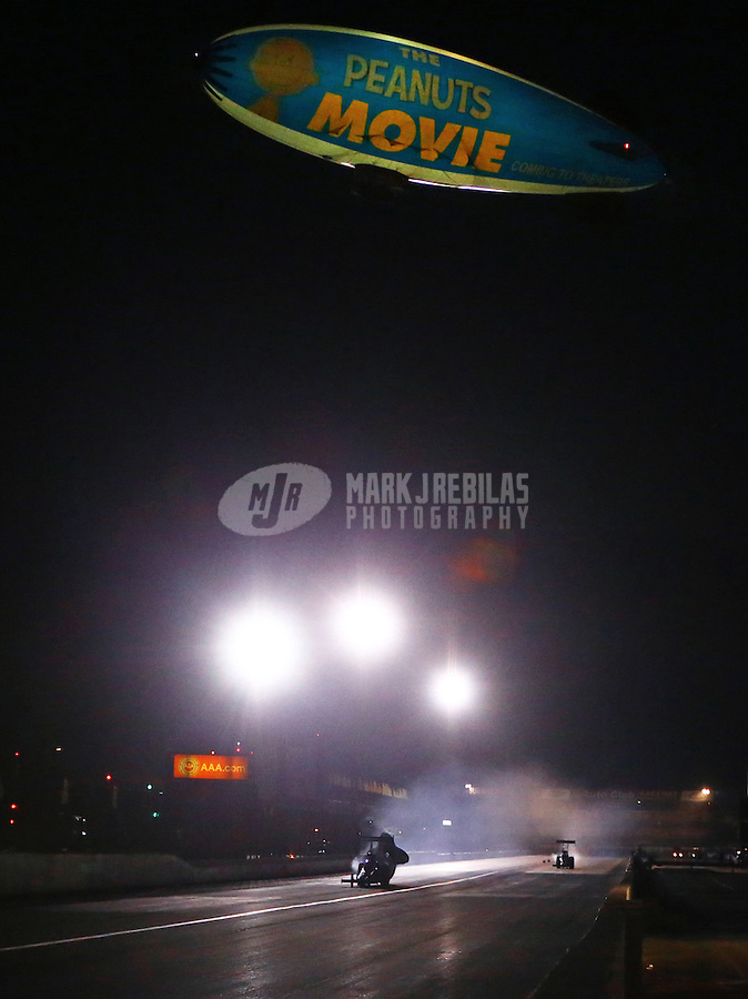 Nov 13, 2015; Pomona, CA, USA; The MetLife blimp with an advertisement for The Peanuts Movie makes a low pass over NHRA top fuel dragster qualifying for the Auto Club Finals at Auto Club Raceway at Pomona. Mandatory Credit: Mark J. Rebilas-USA TODAY Sports