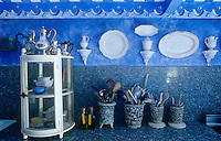 In the kitchen antique white porcelain has been arranged against a blue-and-white trompe l'oeil wall to stunning effect