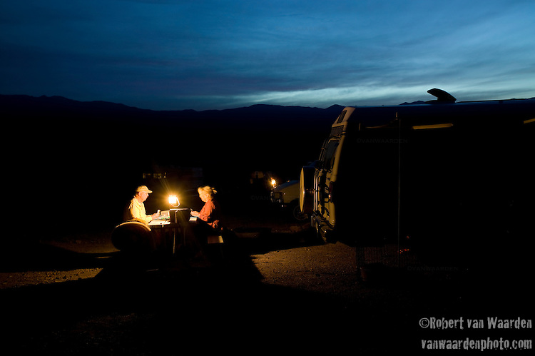 A couple enjoys a game of cards as night descends on Death Valley.