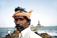 Hindu pilgrims stand on the rocky beach opposite the Vivekananda Memorial and the Thiruvalluvar Statue in Kanyakumari, Tamil Nadu, India on Saturday, 06 January 2007. Kanyakumari is the southern most point in the India.