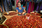 A woman sells chilies in the Tahan Market in Kalay, a town in Myanmar. This market is located in Tahan, the largely ethnic Chin section of the town. She has applied thanaka, a cosmetic paste, on her face.