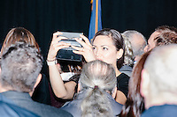 A woman takes a selfie in the crowd while Republican presidential candidate and real estate mogul Donald Trump speaks at a meeting of the New England Police Benevolent Association executive council at the Sheraton Portsmouth Harborside Hotel in Portsmouth, New Hampshire, USA. At the gathering, the group endorsed Trump for president. A small group of perhaps 20 Trump supporters stood outside the hotel and there was a larger group of anti-Trump protesters, mostly across the street. One of the protest organizers estimated that there were around 230 protesters gathered.Many protesters expressed disagreement with Trump's recent statements that he would ban all Muslims from entering the country. Trump brought up the recent shooting in San Berdardino, Calif., at the meeting.