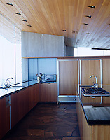The kitchen is functional and sleek with slate flooring and wooden units that mirror the wood clad ceiling