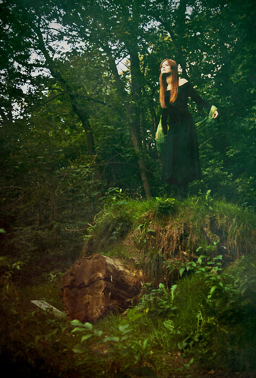 A red haired lady in a black dress, standig on the grass in the forest with sad emotion