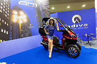 A model poses on a three-wheeled city moped by Adiva at the 44th annual Tokyo Motorcycle show. Tokyo Big Sight exhibition hall, Odaiba, Tokyo, Japan. Friday March 24th 2017. The show runs from Friday March 24th to Sunday March 26th and showcases technological innovations from all the main motorcycle manufacturers along with companies providing protective helmets pads and  clothing to decoration and even camping gear for bike-touring..