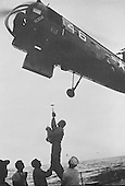 Astronaut John H. Glenn, Jr., is lifted into the recovery helicopter from the USS Noa for transfer to the USS Randolph (CVS-15) on February 20, 1962. Glenn's Friendship 7 Mercury spacecraft landed in an area in the Atlantic approximately 800 miles southeast of Cape Canaveral in the vicinity of Grand Turk Island. He landed 41 miles west and 19 miles north of the planned landing target. Glenn and his spacecraft were recovered by the destroyer USS Noa. The Noa had the spacecraft aboard 21 minutes after landing and Glenn remained in the spacecraft during the recovery operation..Credit: NASA via CNP