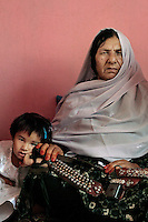 Commander Kaftar poses with her 3-year-old grand daughter Bibi Zora a the safe house she now lives in on the outskirts of Pul-e Khumri, a small city in Bahglan province in Afghanistan. <br /> The only known female Mujahideen commander, Kaftar, was once the leader of a 600-strong armed force. Today she can&rsquo;t even leave the safe house where she is staying as a guest along with her granddaughter. Her enemies, mostly from the neighboring village, are looking for her to settle an old score. According to local accounts, her husband failed to avenge the murder of a relative &ndash; Bibi, as she is called by her eight children, took matters into her own hands and soon after enlisted with the Jamiyat-e-Islami forces of Ahmad Shah Massoud&rsquo;s forces at the height of the Soviet invasion of Afghanistan in the early 80&rsquo;s. Born in Bahglan province, Kaftar is proud to have never surrendered to the Taliban &ndash; in fact, her area of operations never fell to the militants onslaught. Like many other Jihadi commanders, Kaftar surrendered her weapons as part of the UN Disbandment of Illegal Armed Groups program (DIAG) &ndash; however, she kept some small arms for herself and her personal guards. One of these weapons is her Russian-made Makarov pistol, which she always carries on a holster under her shoulder. <br /> Like many other warlords (and former Mujahideen) in Afghanistan, Kaftar used the power of the gun for extortion and self-enrichment. Several residents of her native village of Khoza claim that she is responsible for at least ten deaths along with demanding tax money and extortion from the locals in order to fund her operations. Like many other warlords in Afghanistan, the central and local governments have not made any effort to bring her to justice.