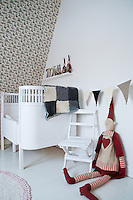 Homemade knitted bunting hangs across the wall of this child's bedroom, its cot hung with a knitted blanket and surrounded by friendly elves